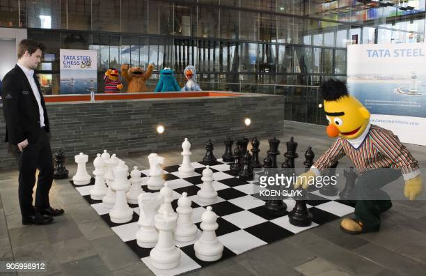 Norwegian chess Grandmaster and World Champion Magnus Carlsen and Sesame Street figure Bert contemplate their moves during a friendly chess match in...