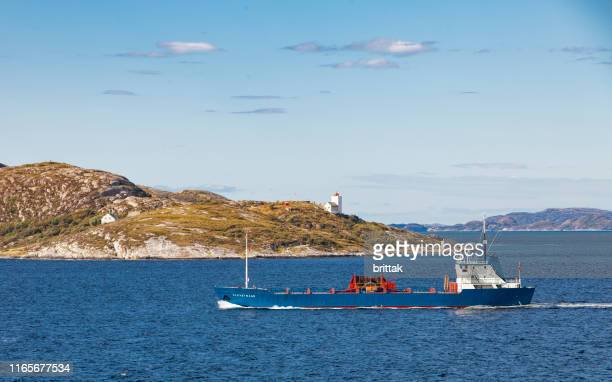 norwegian coast with lighthouse. freighter pasing - industrial ship stock pictures, royalty-free photos & images