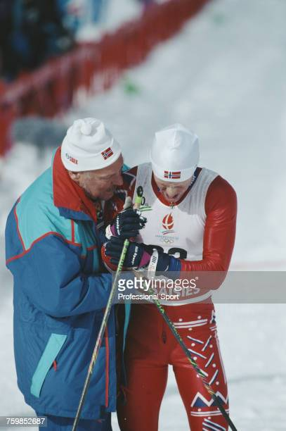 Norwegian crosscountry skier Bjorn Daehlie pictured receiving assistance from a Norwegian team official after crossing the finish line in second...