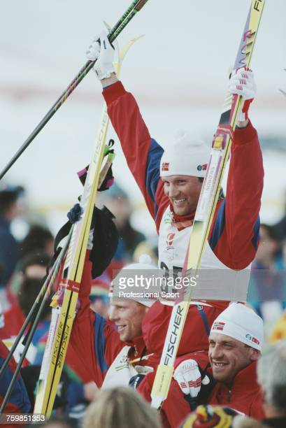 Norwegian crosscountry skier Vegard Ulvang pictured raising his skis in the air in celebration on the medal podium after finishing in first place to...