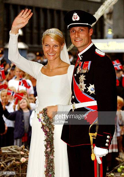 Norwegian Crown Prince Haakon and MetteMarit Tjessem Hoiby wave to wellwishers outside the Oslo Cathedral August 25 2001 after their wedding