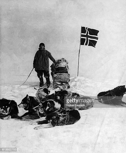 Norwegian explorer stands beside his country's flag.