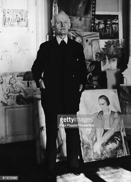 Norwegian expressionist painter and printmaker Edvard Munch with some of his work circa 1920