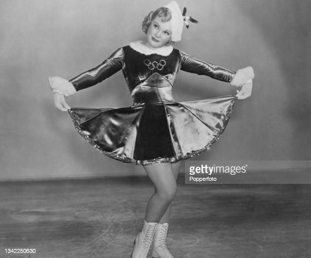 Norwegian figure skater and actress Sonja Henie , wearing a dress featuring the Olympic rings on the chest and a fur collar and cuffs, with Henie...