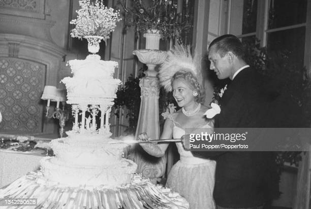 Norwegian figure skater and actress Sonja Henie , wearing her wedding dress, cutting the wedding cake with her husband, American businessman Winthrop...