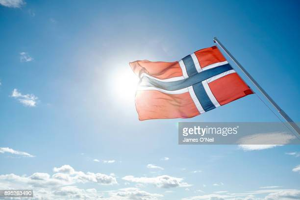 norwegian flag backlit by sun and blue sky, norway - norwegian flag stock pictures, royalty-free photos & images