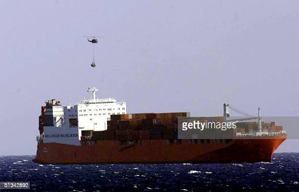 Norwegian freighter Tampa is seen anchored off Christmas Island on 03 September 2001 morning while an helicopter loads supplies for the 438 refugees...