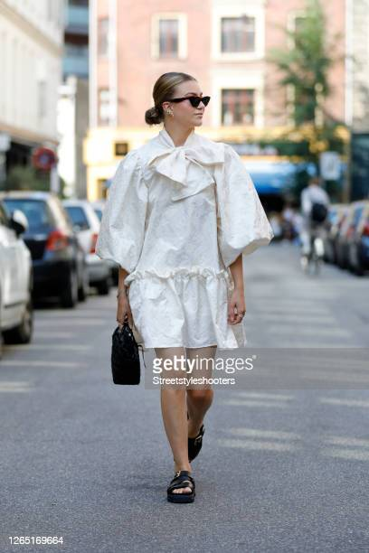 Norwegian influencer Maren Schia wearing a white dress with puff sleeves and a big loop at the collar, a black bag and black sandals seen at...