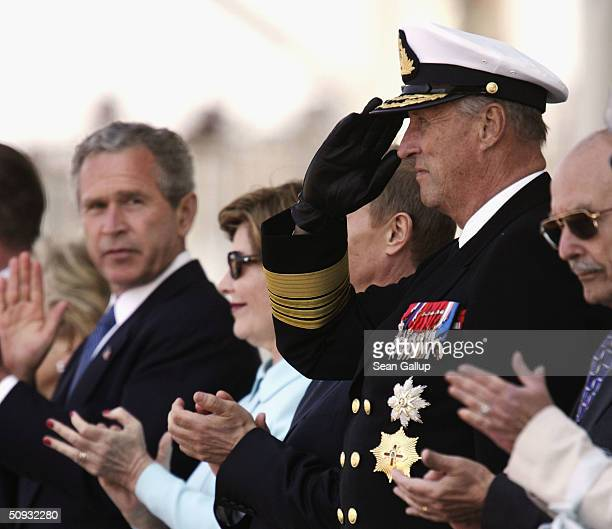 Norwegian King Harald salutes as two Norwegian fighter planes pass by overhead as American President George W Bush looks over during commemoration...