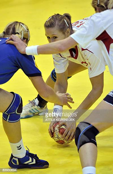 Norwegian Marit Malm Frafjord fights for the ball with Ukrainian Rehina Shymkute during the 8th Women's Handball European Championships match on...