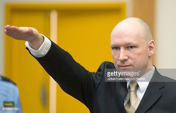 Norwegian mass killer Anders Behring Breivik makes a Nazi salute as he arrives to a makeshift court in Skien prisons gym on March 15 2016 in Skien...