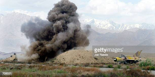 Norwegian mine clearing machine detonates a land mine useing a flail, a series of chains that rotate and beat the ground, April 20, 2002 at the...