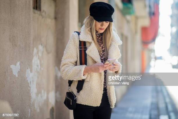 Norwegian model Jeanett Olsen writting a text meassage with her golden Apple Iphone wearing beige teddy jacket Stradivarius sweater with leopard...