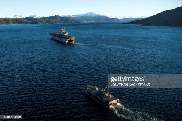 Norwegian Motor Topedo Boat KNM Skudd follows The USS Iwo Jima a Waspclass amphibious assault ship of the United States Navy during the NATO exercise...