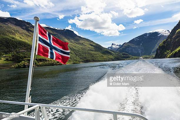 norwegian national flag in a fjord - norwegian flag stock pictures, royalty-free photos & images