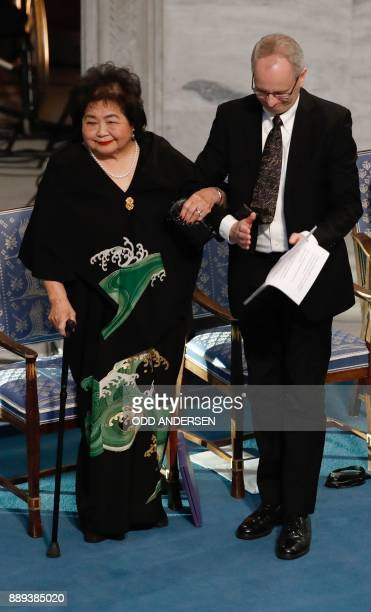 Norwegian Nobel Committee member Henrik Syse helps Hiroshima nuclear bombing survivor Setsuko Thurlow to leave the podium during the award ceremony...