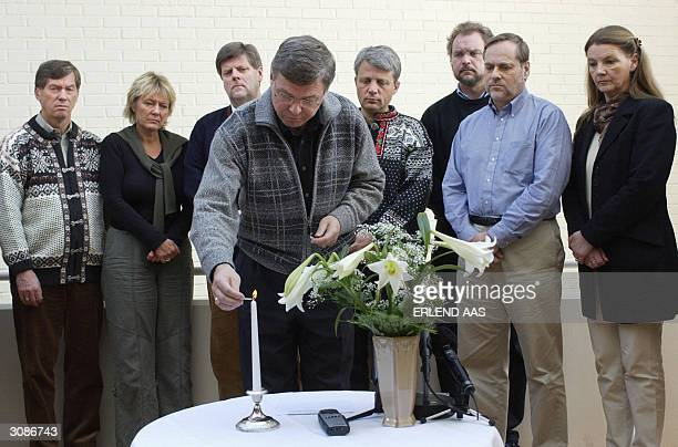 Norwegian Premier Kjell Magne Bondevik lights a candle 15 March 2004 in memory of the victims of the deadly Madrid bombings last week In background...