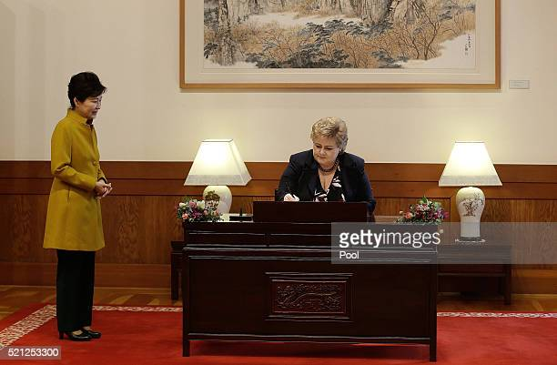 Norwegian Prime Minister Erna Solberg signs the guest book as his South Korean counterpart Park GeunHye watches before a meeting at the presidential...