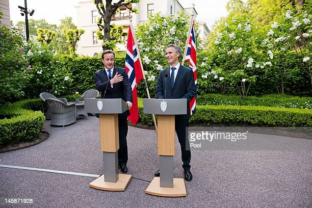Norwegian Prime Minister Jens Stoltenberg and his British colleague David Cameron answer questions during a press briefing in the garden of the...