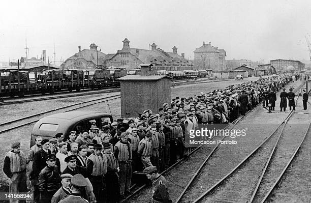 Norwegian prisoners along tracks in the Oslo harbour waiting to be taken aboard and led to concentration camps in Germany Oslo May 1940