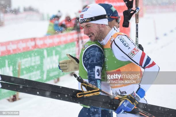 Norwegian skier Jan Schmid is congratulated by Japanese Akito Watabe at the end of the individual Gundersen of the FIS Nordic Combined World Cup on...