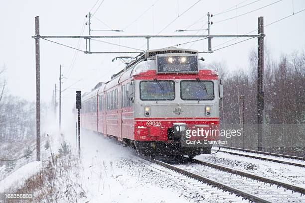 CONTENT] Norwegian State Railways local train passing Lier station on the main line out of Drammen towards Oslo in a cold and snowy day in December...