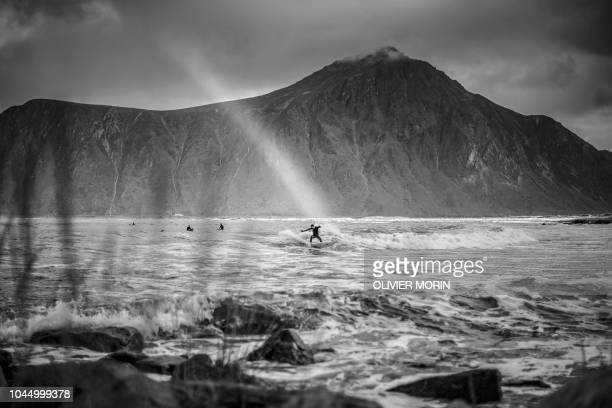 Norwegian surfer Anker Olsen Frantzen rides a wave under a rainbow during a free surf session on September 26 in Flakstad northern Norway at the eve...