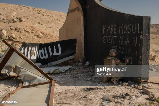 Norwegian volunteer medic writes 'Make Mosul Great Again' on the base of a destroyed Islamic State billboard in west Mosul March 9 2017 Iraqi forces...