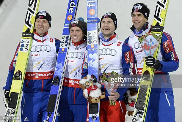 Norwegian's Rune Velta Anders Fannemel Anders Jacobsen and Anders Bardal pose during the winner ceremony of the Men Large Hill Team competition of...
