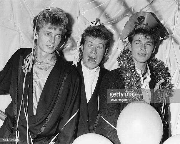 Norweigan pop band 'A-Ha'; Paul Waaktaar-Savoy, Magne Furuholmen and Morten Harket, wearing parts hands and streamers as they celebrate the new year...