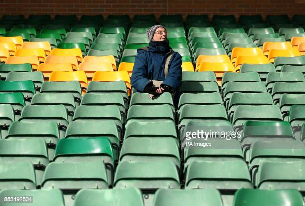 A Norwich City fan sits dejected in the stands as her side is relegated after the Barclays Premier League match at Carrow Road Norwich