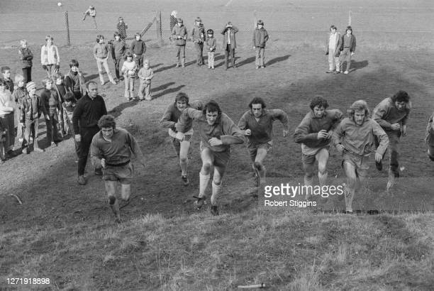 Norwich City FC footballers training for the FA Cup, UK, 27th February 1973. Watching them in the dark tracksuit is manager Ron Saunders.