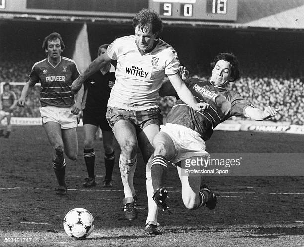 Norwich City football player Mike Channon is tackled by Ipswich Town player George Burley during the Ipswich vs Norwich League Cup Semi Final first...