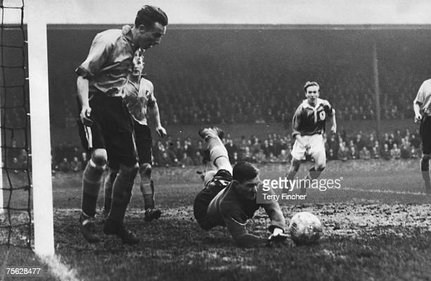 Norwich City goalkeeper Ken Nethercott dives to save during a match against Millwall at The Den 13th November 1954 He is watched by his rightback...