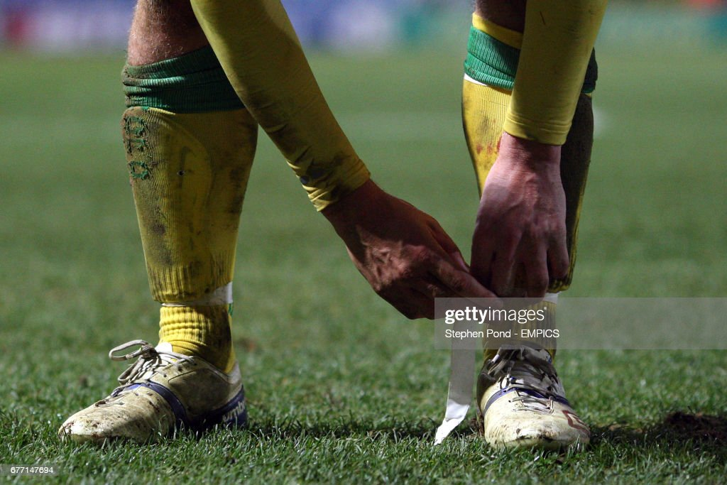 A Norwich City player ties tape around his socks to help keep his shin pads in place