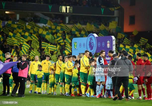 Norwich City players shake hands with Liverpool players prior to the Premier League match between Norwich City and Liverpool FC at Carrow Road on...