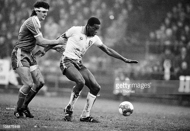 Norwich City striker Justin Fashanu is challenged by Brighton Hove Albion defender Steve Foster during their First Division match played at Carrow...