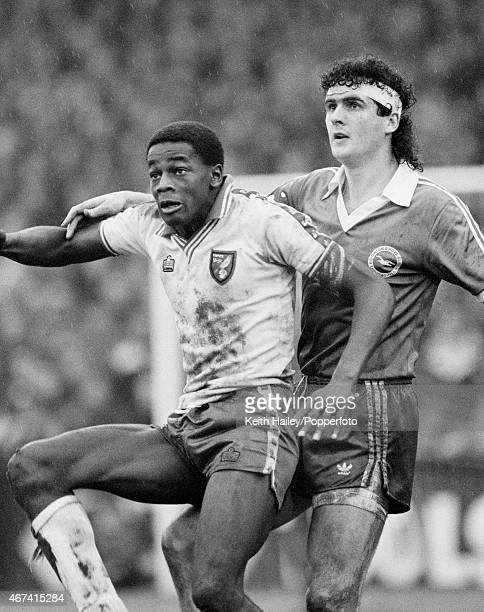 Norwich City striker Justin Fashanu is challenged by Brighton Hove Albion defender Steve Foster during their 1st Division match at Carrow Road in...