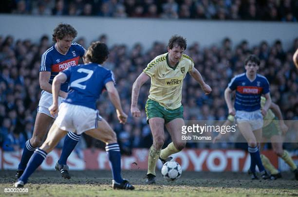 Norwich City striker Mike Channon on the ball, surrounded by Ipswich Town defenders Terry Butcher and George Burley during the Football League Milk...