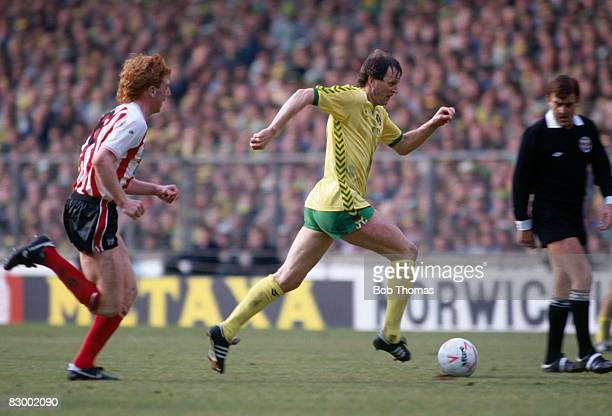 Norwich City striker Mike Channon running with the ball, pursued by Sunderland's David Corner, during the Football League Milk Cup Final at Wembley...