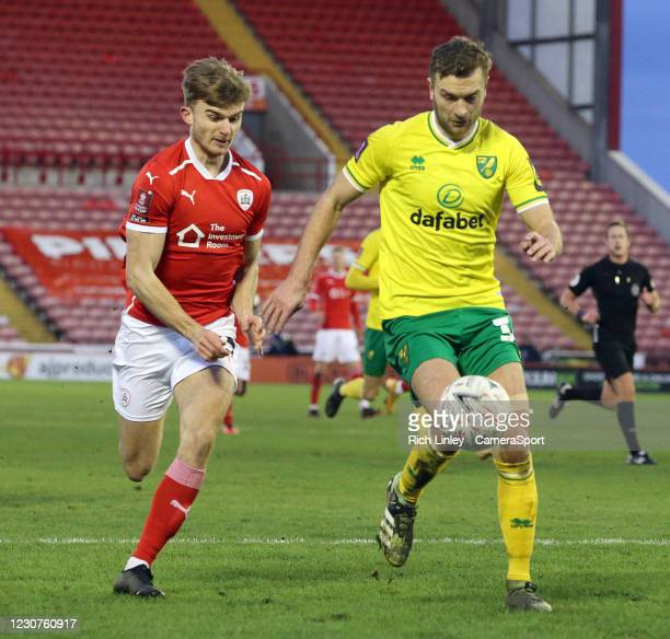 Norwich City's Ben Gibson under pressure from Barnsley's George Miller during the The Emirates FA Cup Fourth Round match between Barnsley and Norwich...