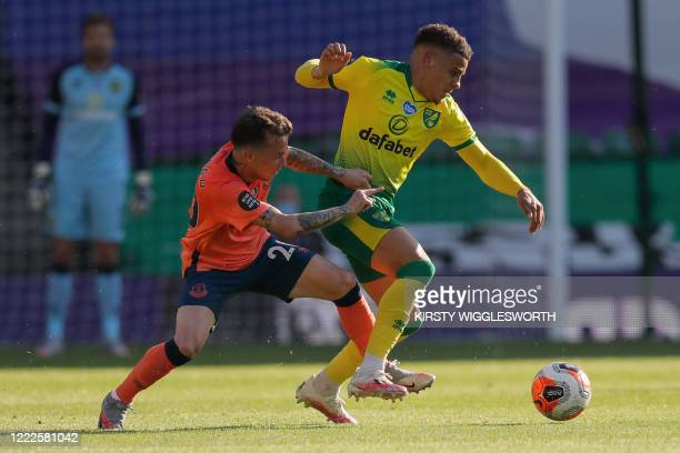 Norwich City's English defender Max Aarons vies for the ball with Everton's Brazilian striker Bernard during the English Premier League football...
