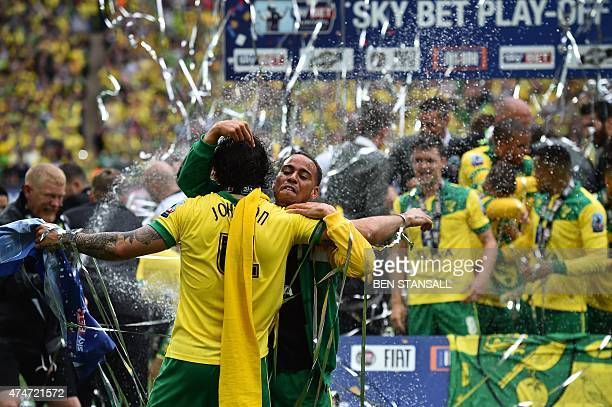 Norwich City's English midfielder Bradley Johnson and Norwich City's English midfielder Elliot Bennett celebrate in front of their team during the...