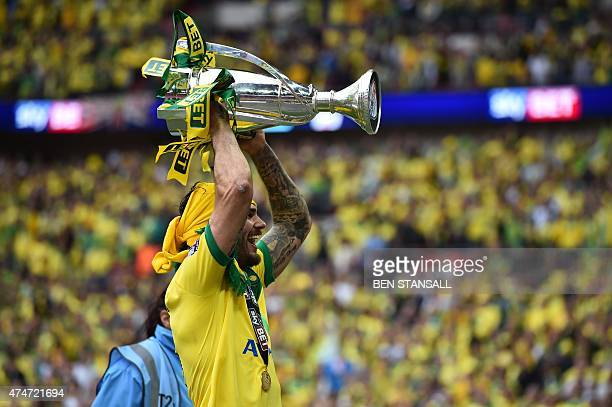 Norwich City's English midfielder Bradley Johnson celebrates with the trophy during the presentation after Norwich City won the English Championship...