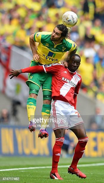 Norwich City's English midfielder Bradley Johnson climbs above Middlesbrough's Ghanaian midfielder Albert Adomah to head the ball during the English...