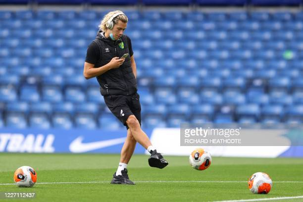 Norwich City's English midfielder Todd Cantwell checks his phone as he warms up before the English Premier League football match between Chelsea and...