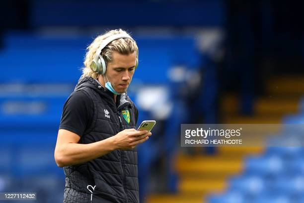 Norwich City's English midfielder Todd Cantwell checks his phone before the English Premier League football match between Chelsea and Norwich City at...