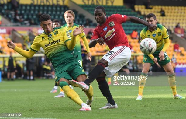 Norwich City's English-born Northern Irish defender Jamal Lewis clocks a shot from Manchester United's Nigerian striker Odion Ighalo during the...
