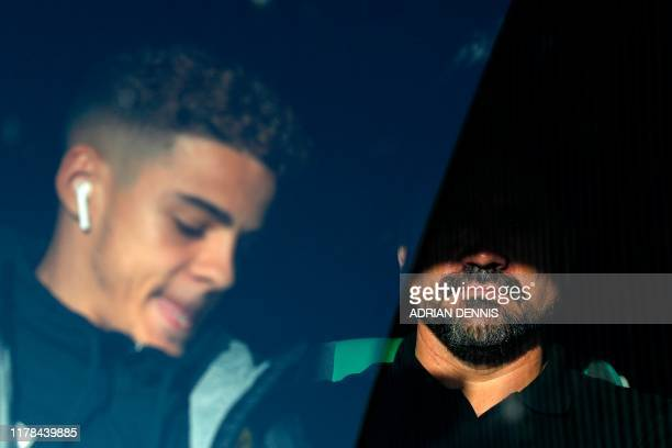 Norwich City's English-born Northern Irish defender Jamal Lewis gets off as Norwich City's German head coach Daniel Farke stays seated as the bus...