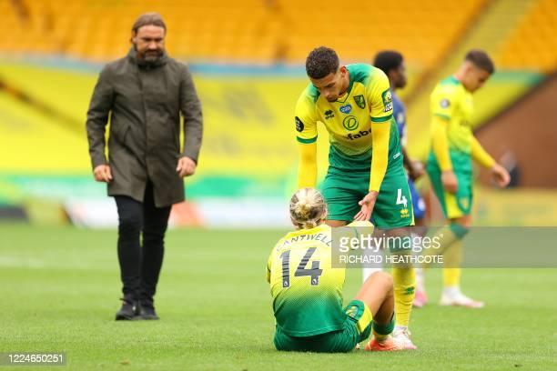 Norwich City's German head coach Daniel Farke watches as Norwich City's English midfielder Ben Godfrey helps Norwich City's English midfielder Todd...